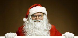 Santa Claus si appoggia in primo piano su un cartello, riportante il logo di Netflix. Il calendario Netflix di dicembre 2018 sarà ricco di regali.