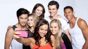 Il cast di Dance Academy si mette in posa per un selfie, dietro hanno uno sfondo bianco