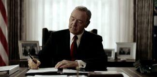 Il presidente Underwood è seduto alla scrivania dello studio ovale. Indossa un completo nero e una cravatta rossa. L'espressione è quella della soddisfazione, mentre firma un editto con una postura piena di sé. E' uno dei tratti distintivi del protagonista di House of Cards