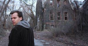 Un biondo protagonista ci da la schiena, ma il suo sguardo si gira sopra la sua spalla, insospettito. Sullo sfondo, alberi spogli e il rudere di una vecchia casa.