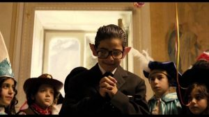 Primo piano del bambino protagonista de La Mafia Uccide solo d'Estate, travestito da Andreotti, in una festa con altri bambini