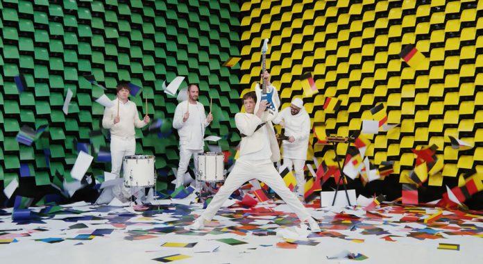 OK Go - Il nuovo sorprendente video Obsession ha come scenografia una parete di 567 stampanti che stampano fogli colorati dietro la band.