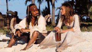 Jack Sparrow ed Elisabeth Swan condividono una spiaggia e una bottiglia di whiskey, in Pirati dei Caraibi La maledizione della prima luna