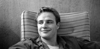 Hollywood sta preparando la biopic su Marlon Brando, qui ritatto da giovane, in mezzo busto, seduto su una poltrona, con un sorriso molto goduto.