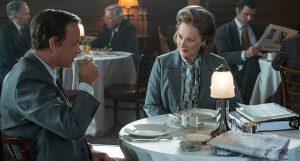 Tom Hanks e Meryl Streep sono seduti ad un tavolo, bevendo caffè e discutendo, in una scena di The Post. La sceneggiatura del film, scritta da Liz Hannah e Josh Singer, è una possibile nominata agli Oscar 2018.