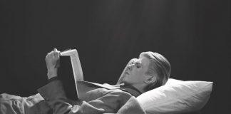 David Bowie legge disteso in una fotografia in bianco e nero, di profilo.